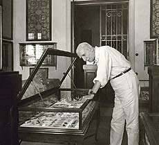 Antonis Benakis observing a case which contains ancient greek jewelry,1940-1950. Benaki Museum Historical  Archives.