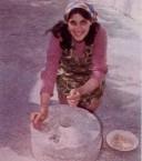 Matina Hiraki grinds corn on a grindstone...