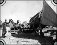 Peter Christianos Snr standing next to a dry rumbler in Lightning Ridge, c. 1961